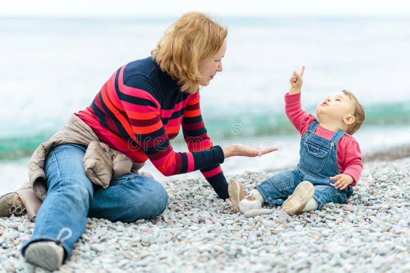 Милый младенец и его мать играя с камешками на пляже стоковые фотографии rf