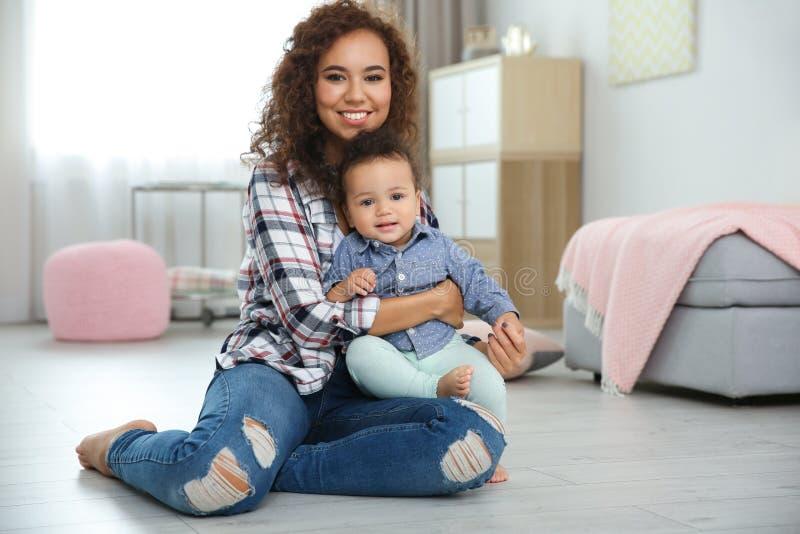 Милый младенец и мать сидя на поле стоковое изображение rf