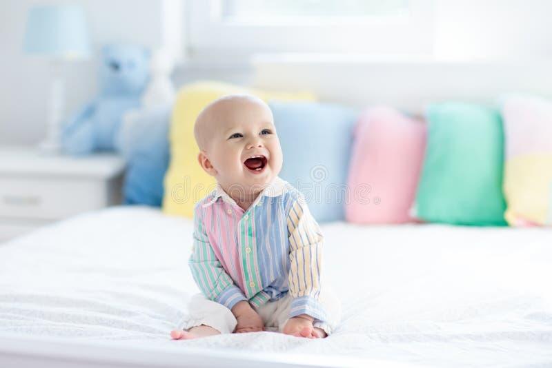Милый младенец на белой кровати стоковое изображение rf