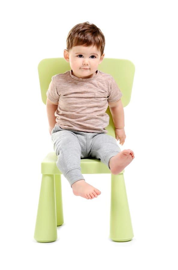 Милый младенец сидя на стуле стоковое фото