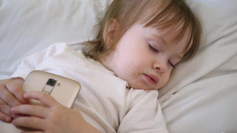 Милый младенец спать в кровати со смартфоном Ребенок лежит на подушке и держит планшет стоковые изображения
