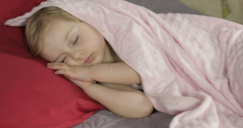 Милый младенец спать на кровати дома Маленькая девочка спать в свете утра стоковые изображения