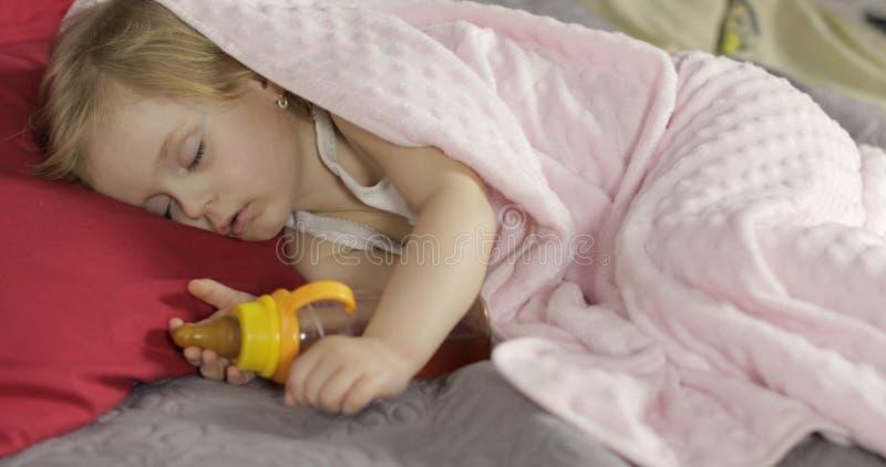 Милый младенец спать на кровати дома Маленькая девочка спать в свете утра стоковое изображение