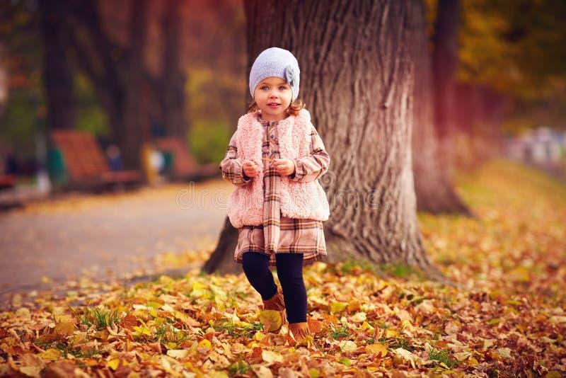Милый модный ребёнок идя в парк осени среди упаденных листьев стоковое фото rf