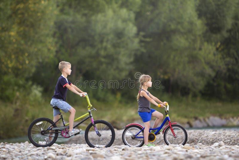 Милый молодой белокурый ребенок катания детей, мальчика и девушки bicycles дальше стоковая фотография