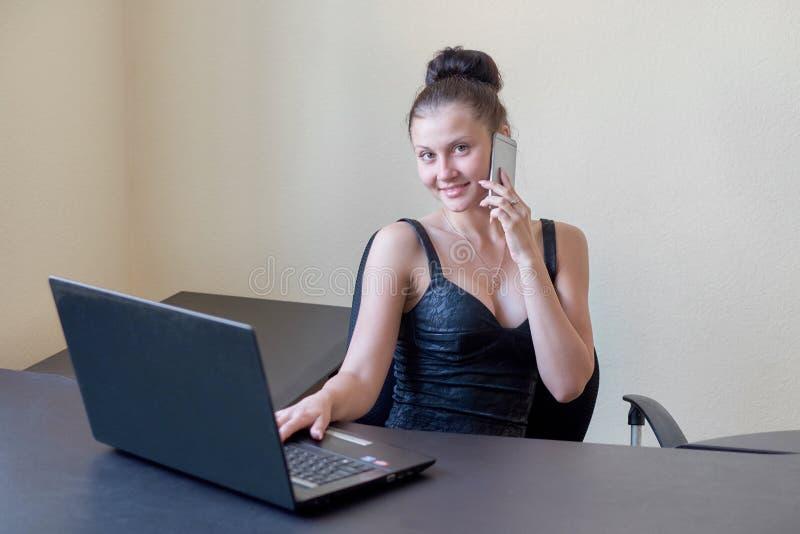 Милый молодой работник офиса в платье вечера говоря на сотовом телефоне в офисе стоковое фото