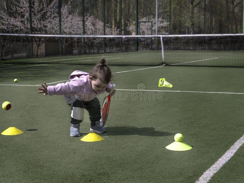 Милый молодой теннисист с ракеткой на теннисной траве корт, детская теннисная тренировка стоковые изображения