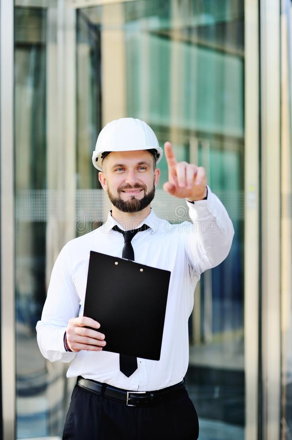 Милый молодой человек с бородой в белых рубашке и связи и белом шлеме конструкции стоковое изображение