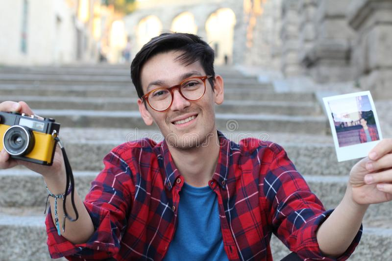Милый мужчина битника держа ретро камеру и немедленное изображение фильма стоковое фото rf