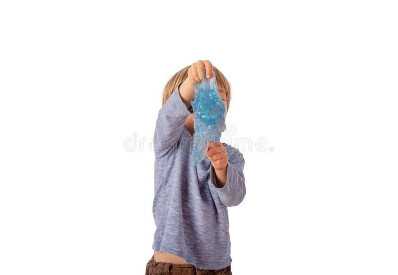 Милый небольшой мальчик держа голубой шлам яркого блеска перед его стороной белизна изолированная предпосылкой стоковая фотография rf