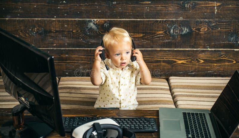 Милый оператор младенца в шлемофоне с компьтер-книжкой Оператор онлайн Обеспечивать самую лучшую поддержку стоковое фото rf