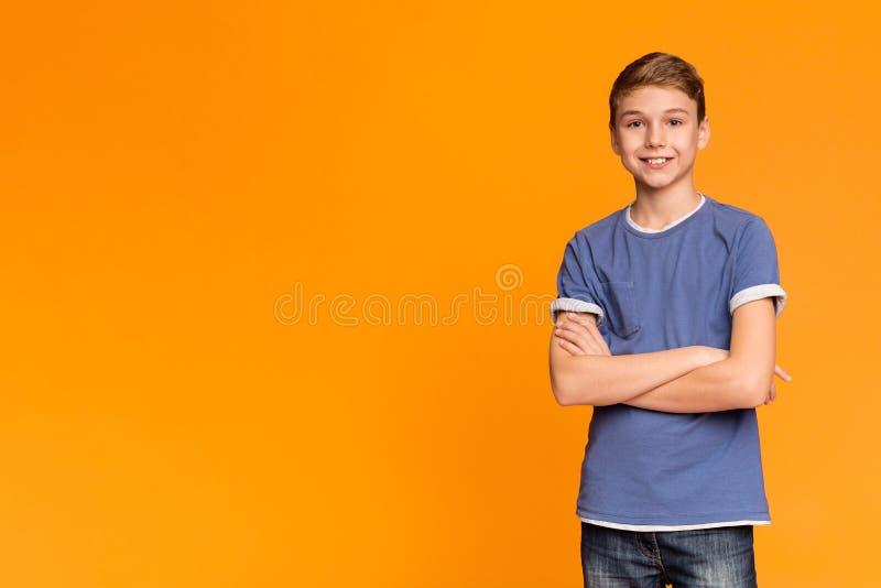 Милый подросток представляя со сложенными руками и усмехаться стоковое изображение