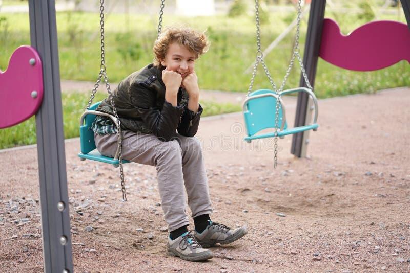 Милый положительный подросток мальчика на спортивной площадке в городе самостоятельно стоковое изображение rf