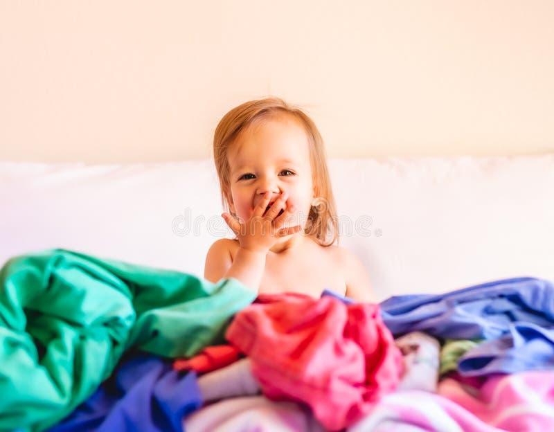 Милый, прелестный, усмехающся, кавказский младенец сидя в куче грязной прачечной на кровати стоковые изображения rf