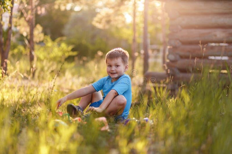 Милый пятилетний мальчик в голубой футболке и шортах сидя на траве летом и играя с игрушками в саде в стоковая фотография