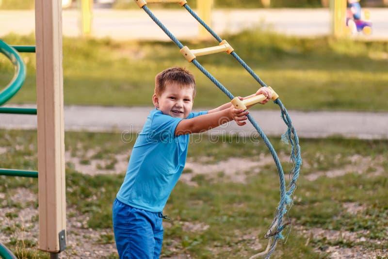 Милый пятилетний мальчик в голубых одеждах спорт летом на спортивной площадке стоковые фотографии rf