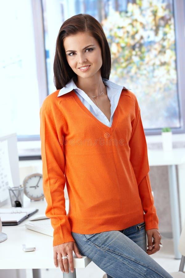 Милый работник офиса ся в померанцовом пуловере стоковая фотография rf