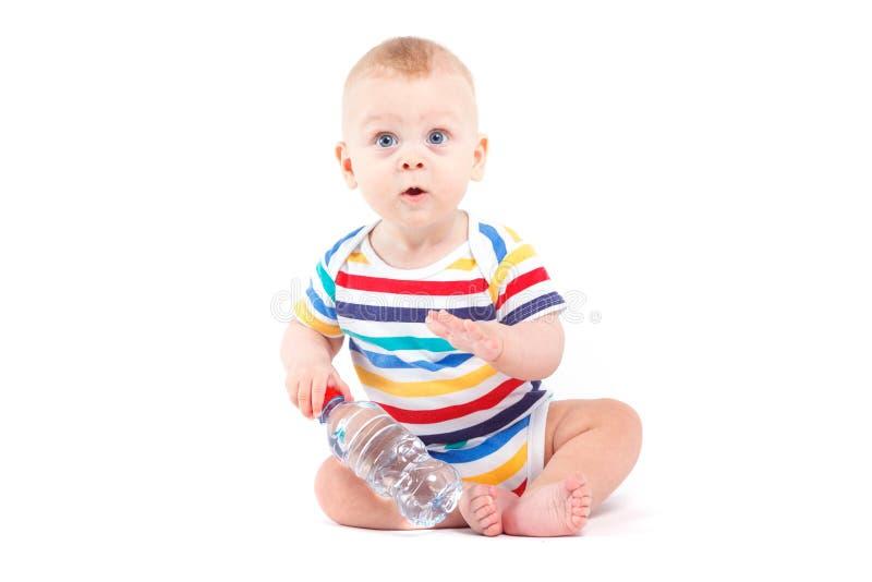 Милый радостный ребёнок в красочной бутылке с водой владением рубашки стоковые изображения