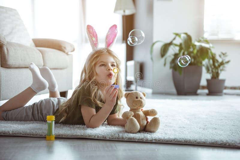 Милый ребенк играя с игрушками в живущей комнате стоковые изображения