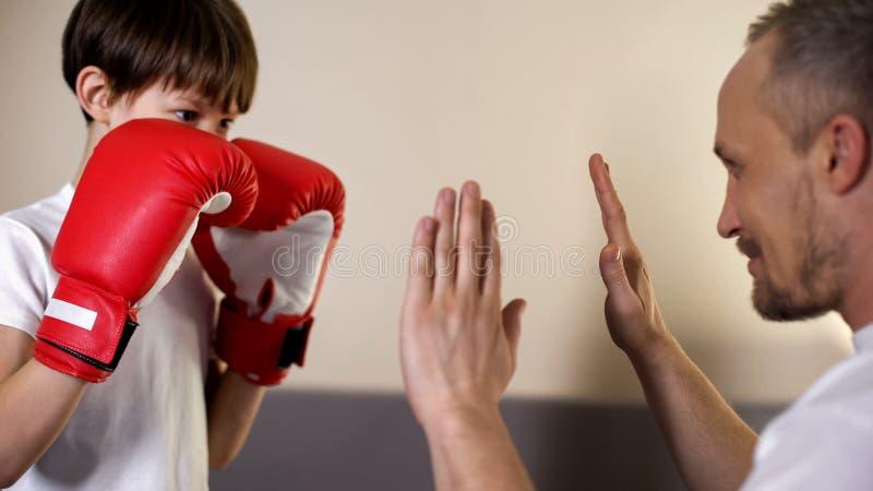 Милый ребенк практикуя кладущ пунши в коробку с его тренером, имеющ потеху с отцом, спорт стоковое изображение