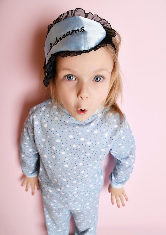 Милый ребенк ребёнка в свете - голубые пижамы и сон маскируют взгляд сверху на пинке стоковая фотография rf