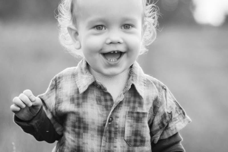Милый ребенок в поле, счастливая усмехаясь сторона стоковая фотография rf