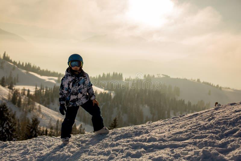 Милый ребенок дошкольного возраста, мальчик, катаясь на лыжах счастливо в австрийце Apls стоковые изображения rf