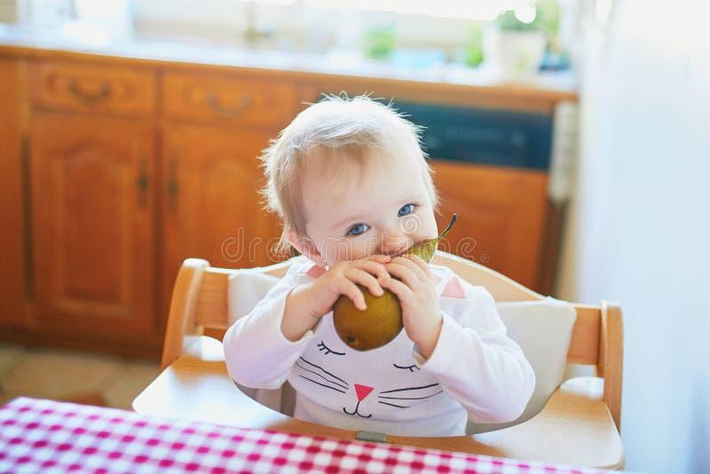 Милый ребенок есть грушу в кухне стоковое фото rf