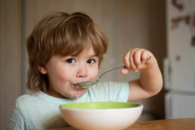 Милый ребенок есть завтрак дома Родительство Еда младенца Молодой парень сидя на таблице есть со смешным стоковые изображения rf