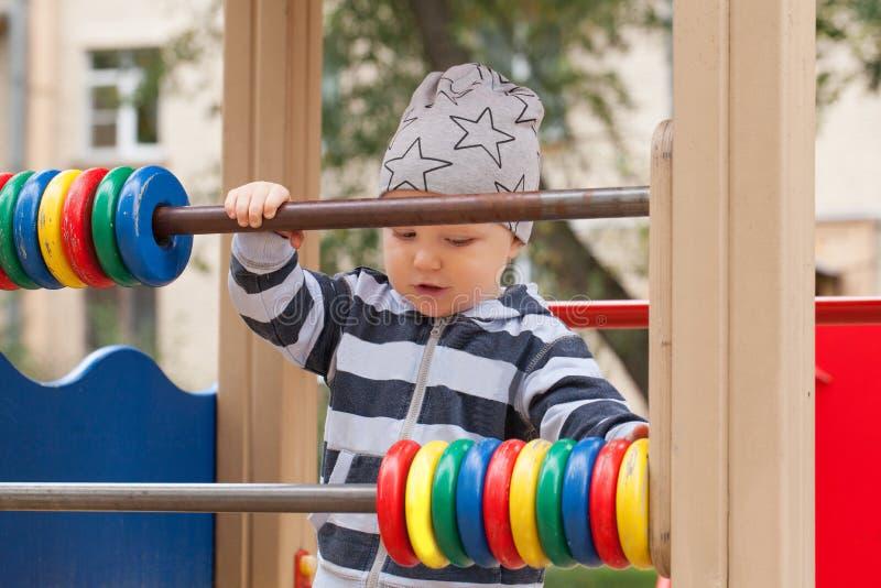Милый ребенок на спортивной площадке Ребенк играя в спортивной площадке outdoors стоковая фотография rf