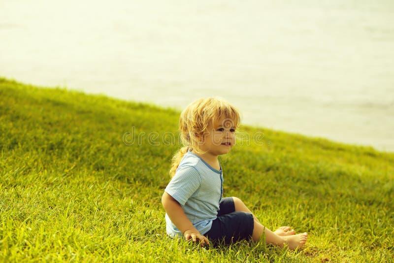 Милый ребенок сидит на зеленой траве стоковые фотографии rf
