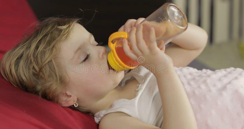 Милый ребенок спать на уютной кровати дома и выпивая соке от бутылки стоковые фотографии rf