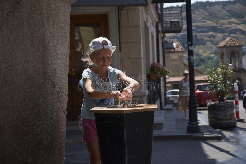 Милый ребёнок выпивая от фонтана воды выпивая в лете стоковая фотография