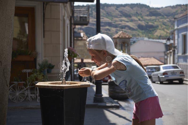 Милый ребёнок выпивая от фонтана воды выпивая в лете стоковые фото