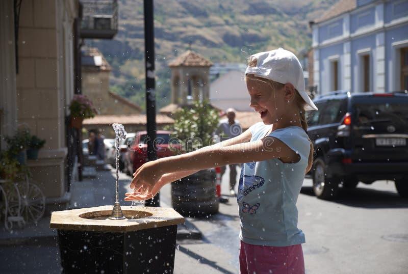 Милый ребёнок выпивая от фонтана воды выпивая в лете стоковое фото