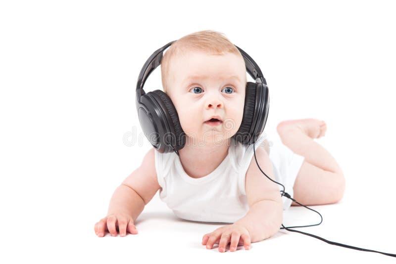 Милый милый ребёнок в белых рубашке и наушниках на голове стоковые фотографии rf