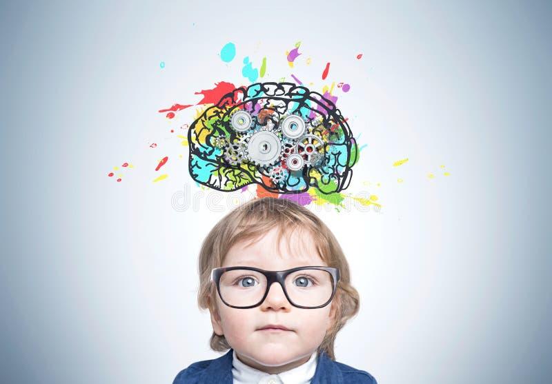 Милый ребёнок в стеклах, cogs мозга стоковое изображение