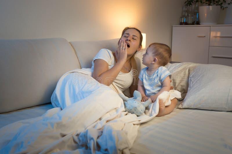 Милый ребёнок сидя в кровати и смотря его утомлял зевая мать стоковое изображение