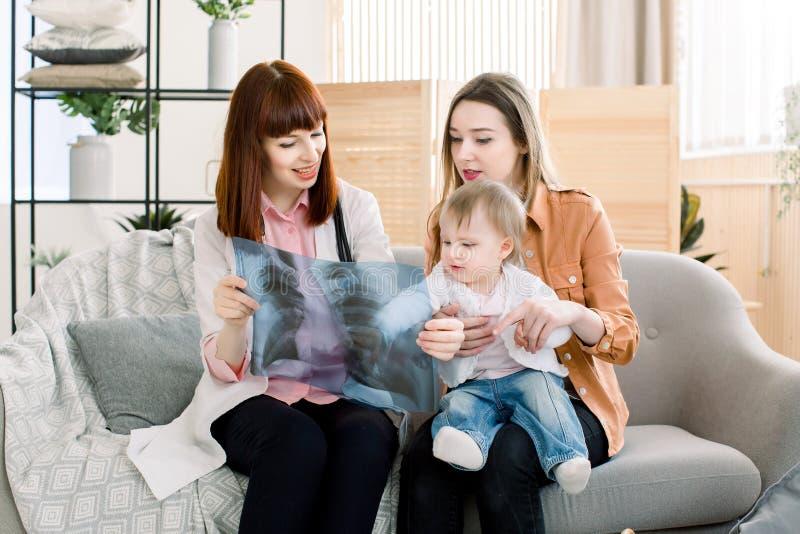 Милый семейный врач женщины показывая изображение рентгеновского снимка к молодой матери с жизнерадостным ребенком на ее руках стоковое изображение rf