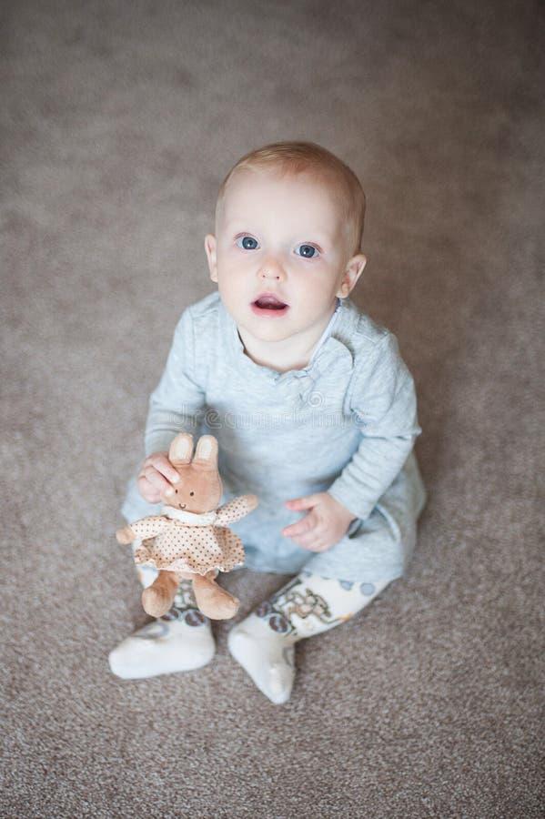 Милый смешной ребёнок с меньшим зайчиком в руке и взгляде на камере Закройте вверх по портрету маленькой девочки с игрушкой в сер стоковая фотография rf