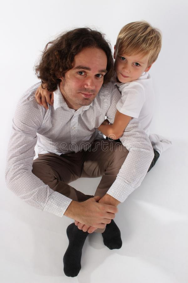 Милый справедливый мальчик ребенка волос обнимая его папы стоковое изображение