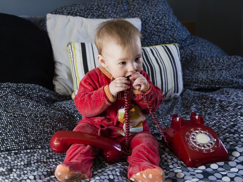 Милый справедливый ребенок сидя на кровати сосать на винтажном красно стоковые фотографии rf