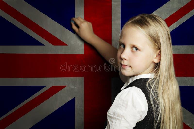Милый студент девушки ребенка против предпосылки флага Великобритании Английская концепция языковой школы стоковые изображения rf