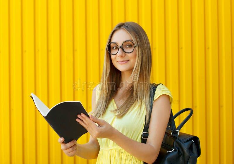 Милый студент девушки smiley при книга нося gla смешной игрушки круглое стоковые изображения