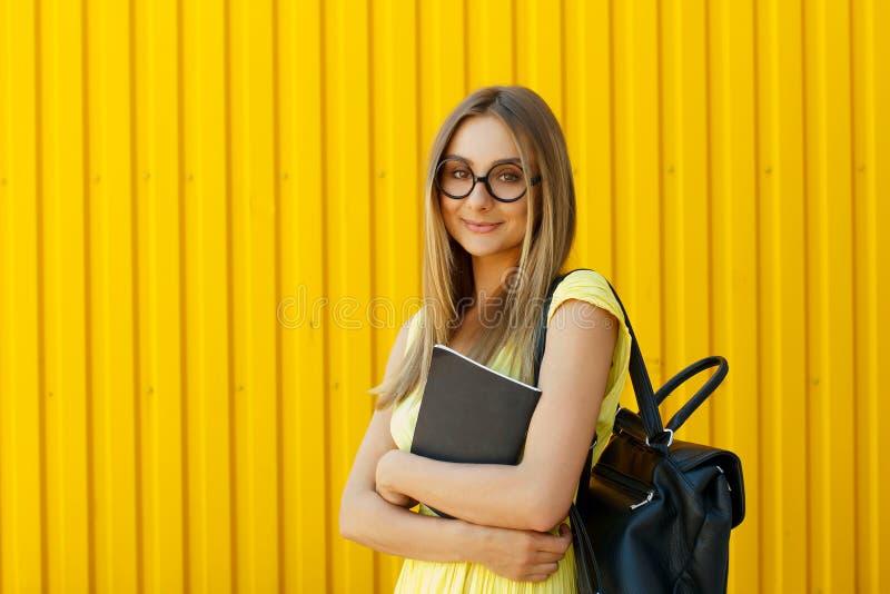 Милый студент девушки smiley при книга нося gla смешной игрушки круглое стоковые фотографии rf