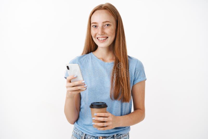 Милый, счастливый женский redhead при веснушки усмехаясь на камере спрашивая совет друга как поступок во время отправки СМС с пар стоковые изображения rf