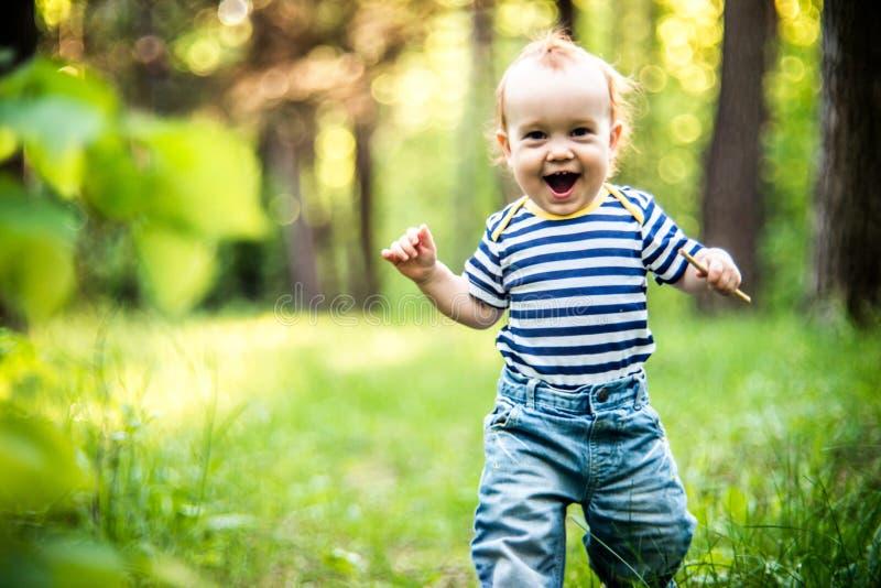 Милый счастливый мальчик ребенка малыша в лесе стоковые изображения
