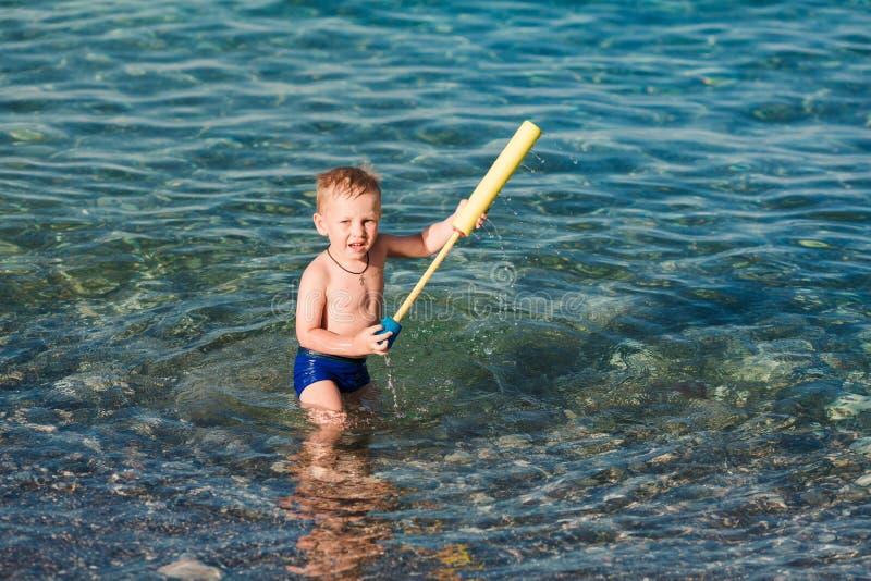 Милый счастливый ребенк играя с пистолетом воды стоковые изображения rf