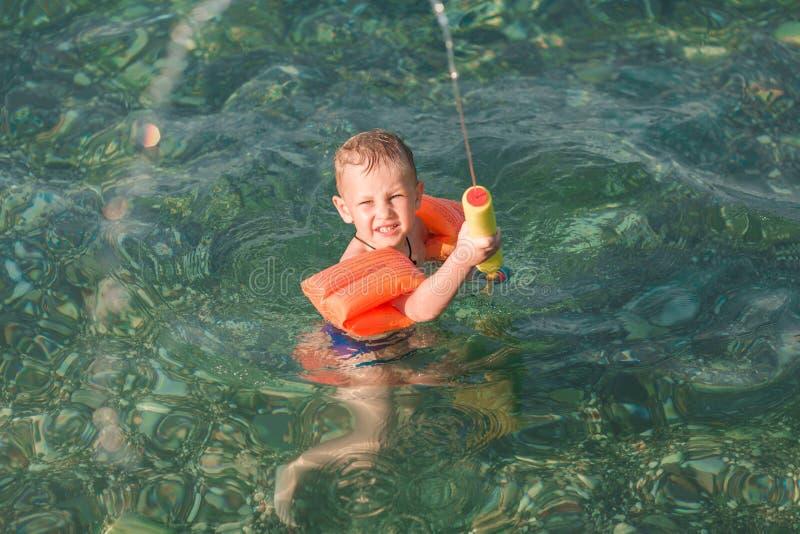 Милый счастливый ребенк играя с пистолетом воды стоковое фото rf