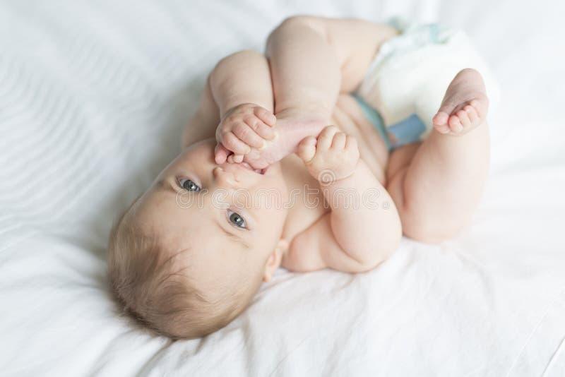 Милый счастливый ребёнок 7 месяцев в пеленке лежа и играя стоковые фотографии rf
